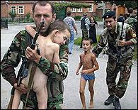 Soldados llevando a niños en Beslan